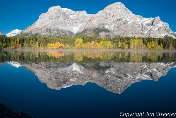 Aspens reflected in Wedge Pond in the Kananaskis valley of Alberta, Canada. Kananaskis is one of the valleys located in the Canadian Rockies and is located east of Banff and west of Calgary.