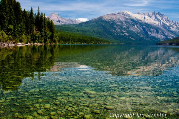 Glaciated peaks reflect in the clear,still water of Kintla Lake in Glacier National Park, Montana on a summer afternoon. The image was taken from a kayak. Kintla is accessed by a rough road that travels up the North Fork almost to the Canadian border.