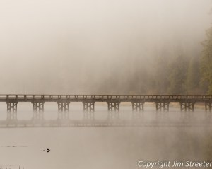Morning fog shrouds the bridge over the Clearwater River at the southern end of Seeley Lake in western Montana.