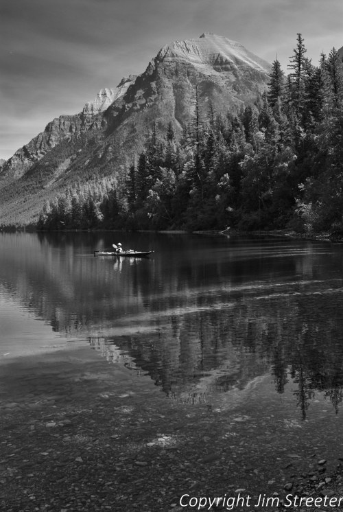 A lone kayaker floats on the still water of Bowman Lake in Glacier National Park on an August afternoon.