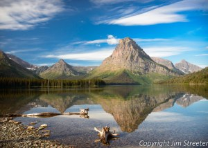 Sinopah Mountain reflects in lower Two Medicine Lake on a summer morning. Two Medicine is located on the east side of Glacier National Park in Montana.