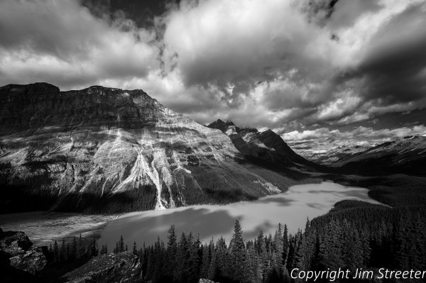 Peyto Lake, along the Icefields Parkway in Banff National Park, shimmers under breaking clouds from a recent fall storm. Peyto Lake is a glacier-fed lake in the Canadian Rockies that gets its turquoise color from glacial rock flour suspended in the water.