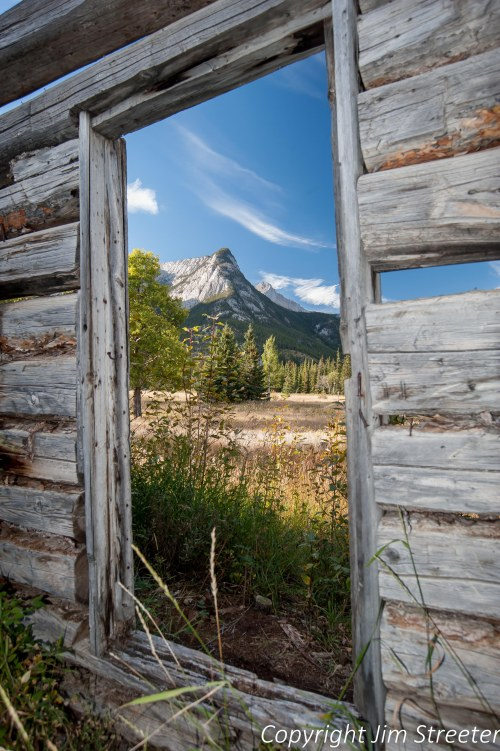 The Canadian Rockies appear through the window frame of an old cabin on the Moberly homestead near Jasper, Alberta. Ewan and Madeline Moberly and other families were early settlers in the area at the end of the 19th century.