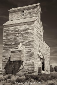 "A old wooden and weather-beaten grain elevator stands in Rudyard, Montana. This area is known as the ""golden triangle"" for the vast acreage devoted to grain production."