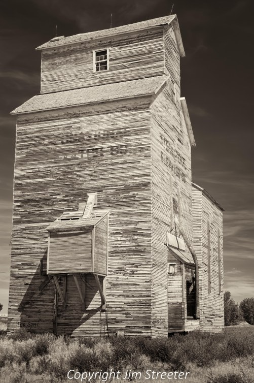 """A old wooden and weather-beaten grain elevator stands in Rudyard, Montana. This area is known as the """"golden triangle"""" for the vast acreage devoted to grain production."""