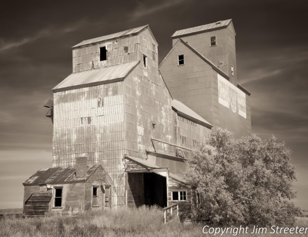 Two old time wooden grain elevators still stand in Inverness, Montana.