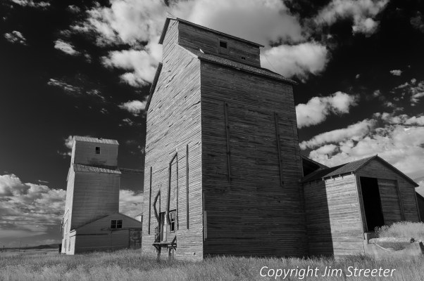 """An old-fashioned wooden grain elevator sits next to its modern aluminum cousin outside of Walthom, Montana. This area is known as the """"golden triangle"""" for the vast acreage devoted to grain production."""