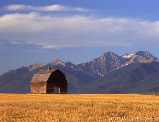 An old barn stands against the Mission Mountains outside of Arlee, Montana on a fall afternoon.