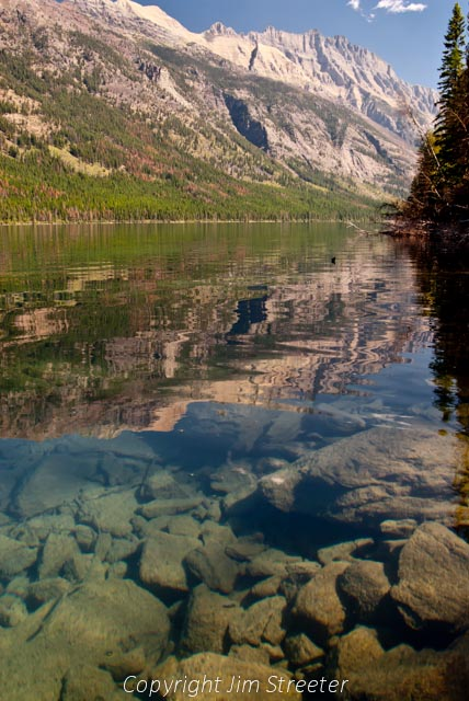 Bowman Lake reflects the surrounding mountains in Glacier National Park in Montana.