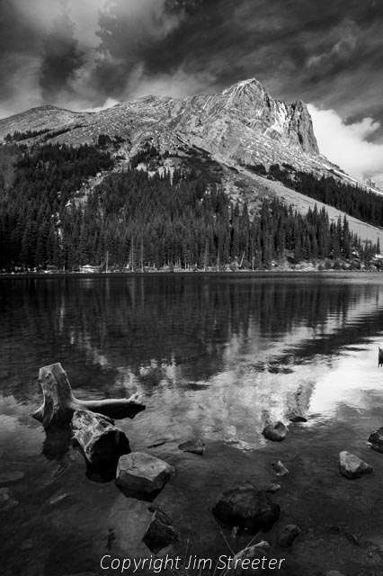 The mountains are reflected in Elbow Lake in Kananaskis Provincial Park in Alberta Canada.
