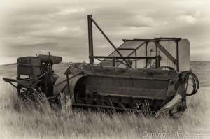 An antique piece of harvesting equipment lies abandoned on an old farm outside of Choteau, Montana.