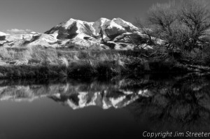 Emigrant Peak, part of the Absaroka range in southwestern Montana, is reflected in a small pond on a cattle ranch on a winter afternoon.