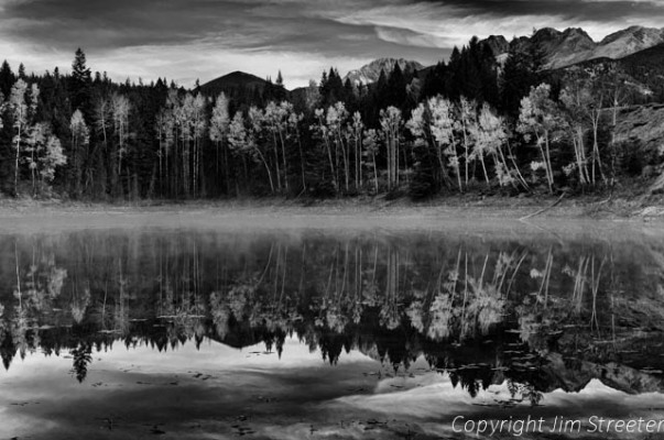 Mist rises from a small roadside pond on fall morning in Kootenay National Park in the Canadian Rockies.