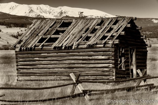 An old cabin still stands as Pintlar range rises in the distance from the Mount Haggin Wildlife Management Area south of Anaconda, Montana.