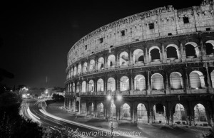 Headlights blur as nighttime traffic streams around the Colosseum in Rome, Italy. The Coliseum is lit from the inside at night, hightlighting each arch in the 1,945 year old structure.