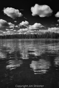 Summer clouds scud across the sky, reflecting in Seeley Lake in western Montana.