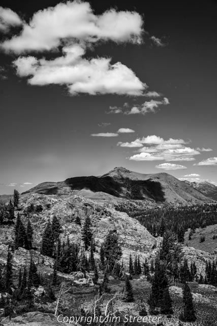 Scattered summer clouds cast shadows over the Sierra peaks as seen from the Woods Lake Loop trail near Round Top Lake. The loop travels through the Mokelumne Wilderness, passing Round Top and Winnemucca lakes.