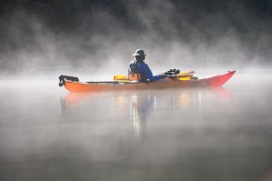 A kayaker paddles through the morning mist on Cameron Lake in Waterton Lakes Lakes National Park in Alberta, Canada. Waterton is the northern part of Waterton-Glacier International Peace Park which straddles the US-Canada border.
