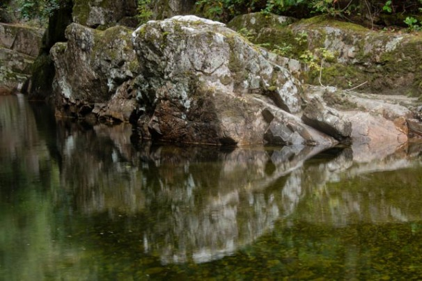 Granite rocks reflect in the still water along the edge of a pool on Chapman Creek above Sechelt, British Columbia. Sechelt is located in the southern part of the Sunshine Coast of western Canada.