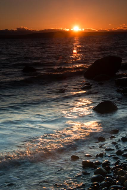 The last rays of the setting sun light up the rocky shore along Malaspina Strait outside of Powell River, British Columbia. Powell River is located along the northern Sunshine Coast in western Canada.