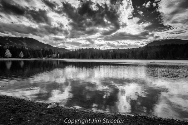Autumn clouds from a coming storm reflect in Lost Lake in Whistler, British Columbia in Canada.