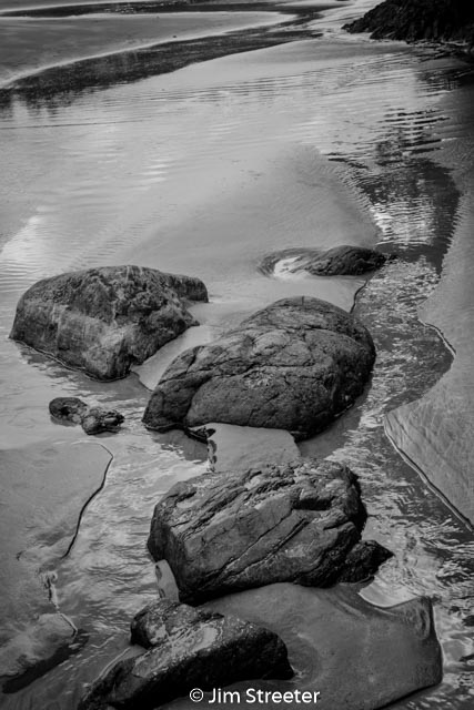 The outgoing tide carves channels in the sand around rocks on the beach at Cox bay outside of Tofino, British Columbia in Canada.