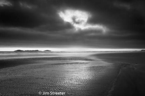 The setting sun peers through a hole in the clouds at Combers Beach in Pacific Rim National Park outside of Tofino, British Columbia.