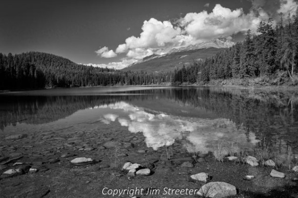 Clouds reflect in Mina Lake on a fall afternoon in Jasper National Park in Alberta, Canada.