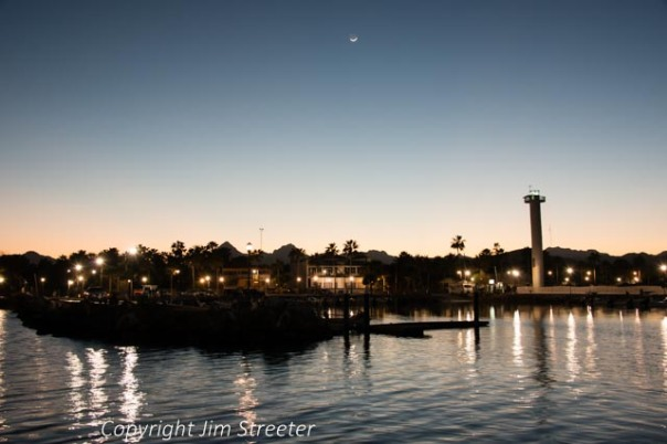 Sunset silhouettes the lighthouse and waterfront of Loreto in Baja California Sur in Mexico on an early spring evening. Loreto is located on the east shore of the peninsula on the Sea of Cortes.