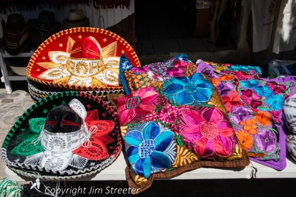 Colorful hats and pillows are arranged for sale by a street market vendor in Loreto in Baja, Mexico. The table was part of a market set up near the Mision Loreto in the city center.