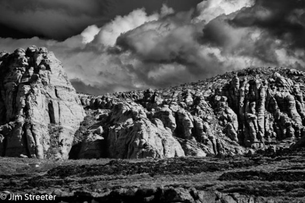 Clouds move in over the sandstone cliffs n a spring day in Snow Canyon State Park in Utah . Snow Canyon is located in southwest Utah near St. George. It boast red and white sandstone with the remnants of lava flows and cinder cones, making for a stunning, multi-colored desert landscape.