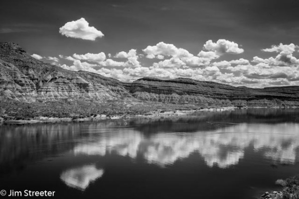 Clouds and sandstone cliffs reflect in Quail Creek Reservoir on a spring afternoon. The reservoir is located in Quail Creek State Park north of St. George, Utah.