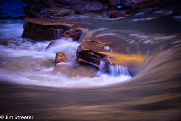 Water cascades over rocks in the Virgin River on a spring morning in Zion National Park in Utah.