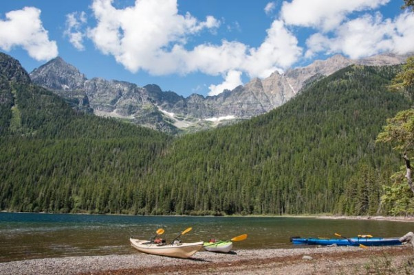 Three kayaks sit on the shore at the head of Bowman Lake, just east of the backcountry campground in Glacier National Park. Bowman Lake is located in a remote area along the western edge of the park in Montana.