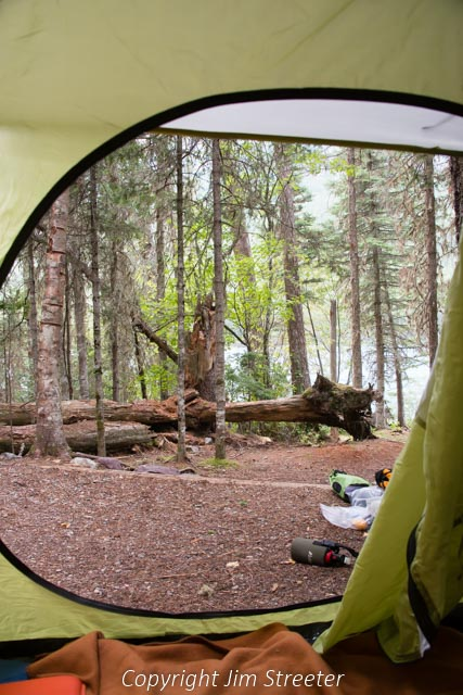 The tent flap opens to reveal the backcountry campground at Bowman lake with the lake just beyond the trees. The campground lies about seven miles from the west shore of Bowman lake in Glacier National Park in Montana.