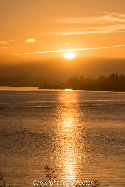 Looking out from the ferry terminal at Anacortes, Washington, a summer sunrise glows off the calm waters of Puget Sound.