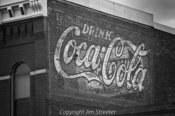 An old advertisement for Coca-Cola is painted on the side of a brick building in the historic district of Livingston, Montana.