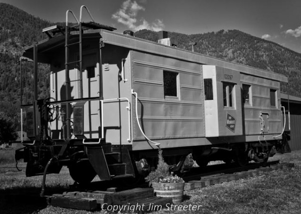 "A antique Milwaukee Road caboose sits on a siding in Alberton, Montana. The Milwaukee Road line was the shortest line over the continental divide, having been built between 1906 and 1909. Portions of the ""Pacific Extension"", which included western Montana and the Idaho panhandle, were electrified to reduce the risk of wildfires along the route."
