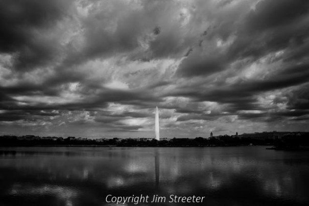 The Washington Monument reflects in the pool on the National Mall under scudding clouds on a fall afternoon. The monument is an obelisk built to commemorate George Washington, the first American president. It stands 554 feet, 7 11/32 inches tall.