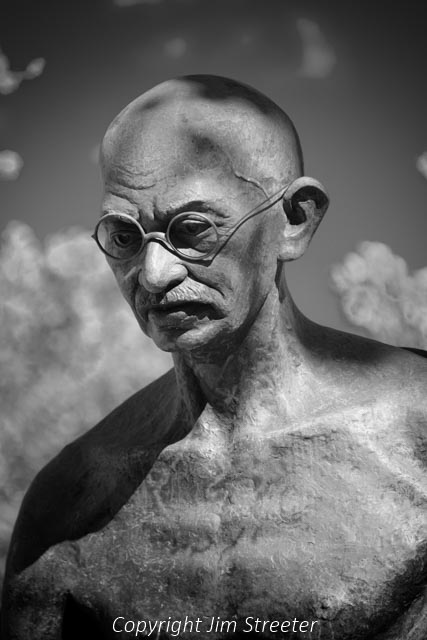 """A statue of Mahatma Gandhi sits in front of the embassy of India in Washinton DC. It depicts him in ascetic garb as he was seen in a 1930 march against a salt tax in India. The inscription on the statue reads, """"my life is my message."""""""