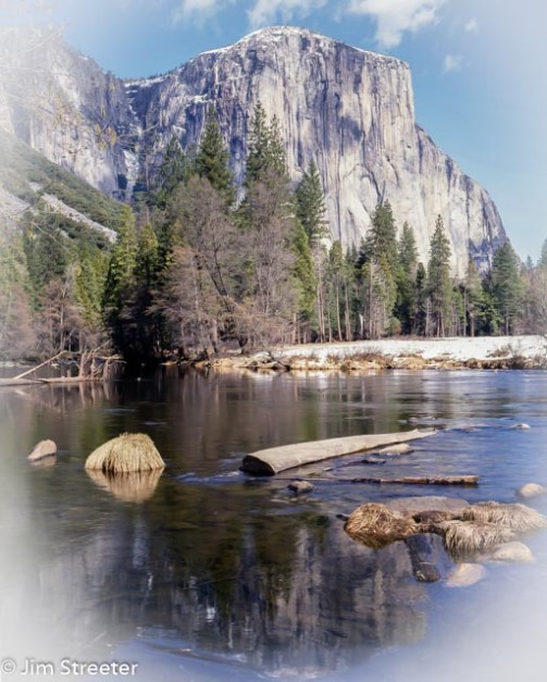 The 3000-foot granite monolith of El Capitan looms over the Yosemite Valley in California. Under a thin cover of snow, it reflects in the Merced river on a winter day.