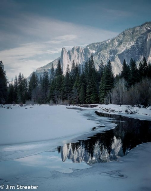 """The peaks of the Three Brothers reflect in the unfrozen water of the Merced River on a winter day. The Three Brothers are comprised of Eagle Peak, the uppermost """"brother"""" and Middle and Lower brothers."""