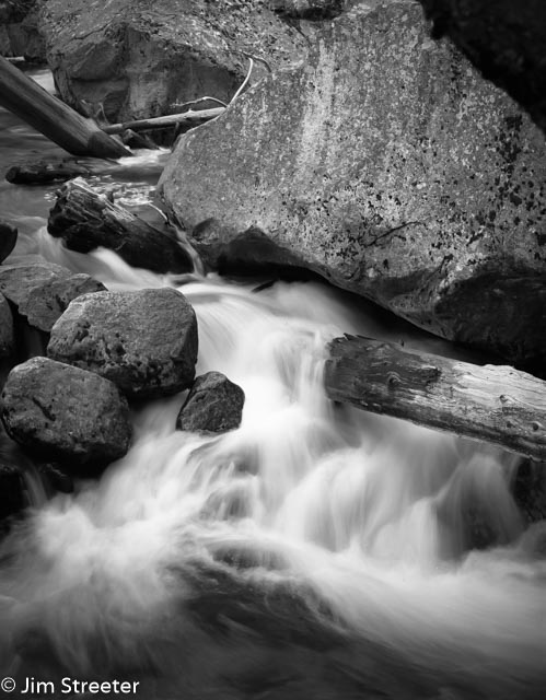 The Merced River rushes downstream over and around granite boulders on its way out of Yosemite National Park in California.