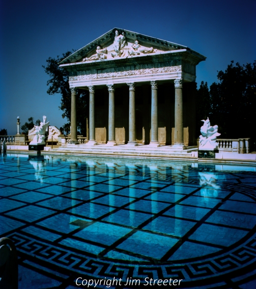 The Neptune Pool at Hearst Castle in San Simion, California, reflects the temple structure that stands along one side. The final Neptune Pool was built from 1934-36 and is the third version of the pool. The pool is 104 feet long and grows from 58 feet wide at one end to 95 feet wide at the other end.