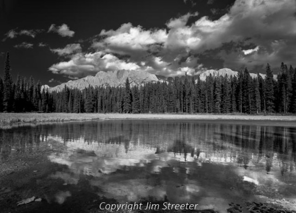 A pond near Marl Lake reflects the surrounding peaks of the Canadian Rockies and afternoon clouds on an early fall afternoon. Marl Lake is located in the Kananaskis Valley of Alberta, Canada.