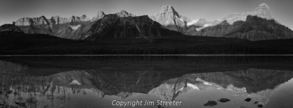 The rising sun lights the peaks of the Continental Divide on the west side of Lower Waterfowl Lake, just north of Bow Summit along the Icefields Parkway in Banff National Park, Alberta, Canada.