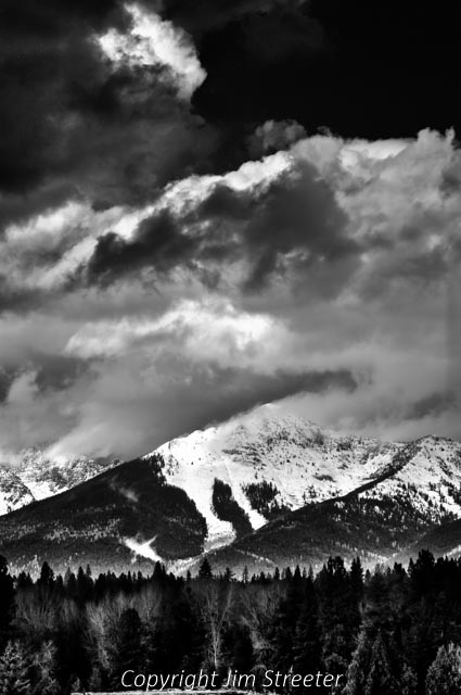 Sunlight filters through winter clouds, highlighting the Swan Range, which runs along the eastern side of the Seeley-Swan valley in western Montana. Over the ridges of the Swan Range lies the Bob Marshall Wilderness.