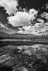 Clouds reflect in Lower Basin Creek lake in the Beartooth mountains on a summer day. The Beartooth mountains extend from Red Lodge, Montana to the northwest corner of Wyoming near Yellowstone National Park.